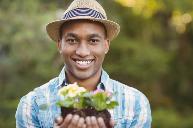Uśmiechnięty Mężczyzna Trzyma Kwiaty W Ogródzie Premium Zdjęcia
