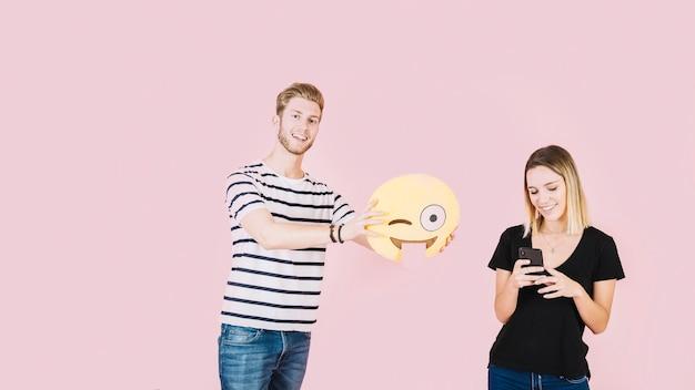 Uśmiechnięty mężczyzna trzyma mrugać emoji ikonę blisko kobiety używa telefon komórkowego Darmowe Zdjęcia