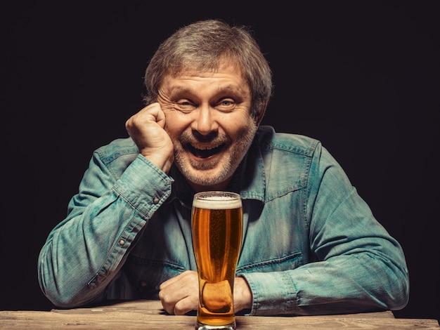 Uśmiechnięty Mężczyzna W Dżinsowej Koszuli Ze Szklanką Piwa Darmowe Zdjęcia