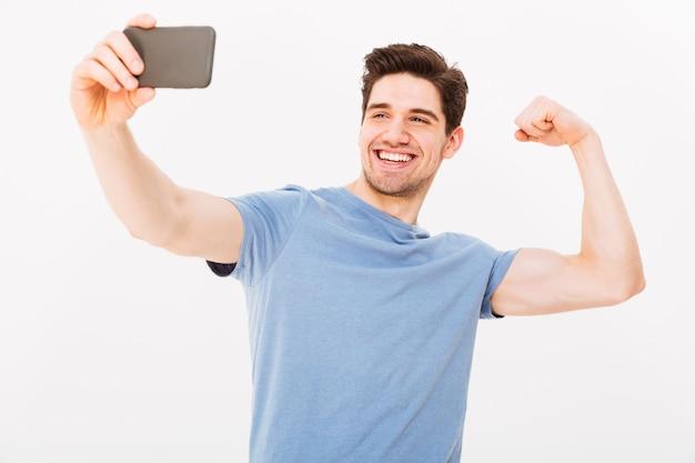 Uśmiechnięty Mężczyzna W Koszulce Robi Selfie Na Smartphone Podczas Gdy Pokazywać Jego Biceps Nad Szarości ścianą Premium Zdjęcia