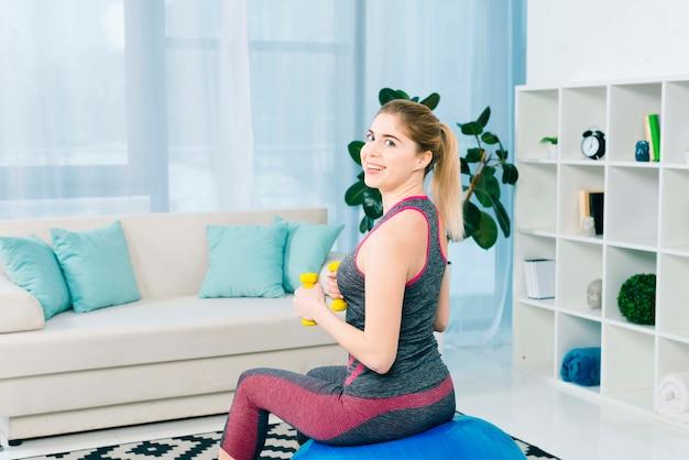 Uśmiechnięty młodej kobiety obsiadanie na sprawności fizycznej piłce ćwiczy z żółtymi dumbbells Darmowe Zdjęcia