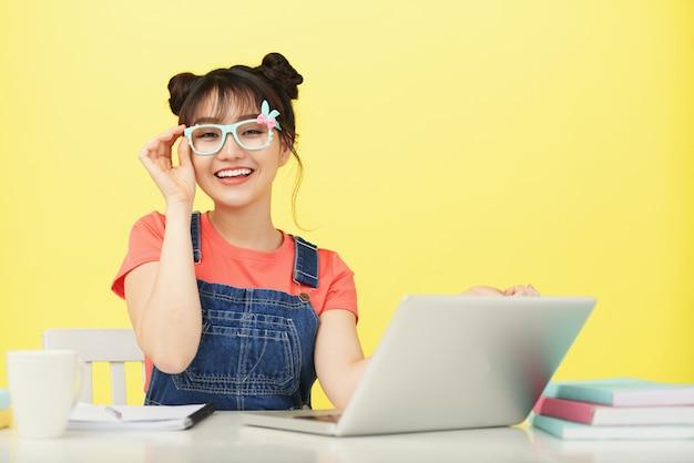 Uśmiechnięty młody azjatycki żeński uczeń siedzi przy biurkiem z laptopem w jaskrawo coloured szkłach Darmowe Zdjęcia