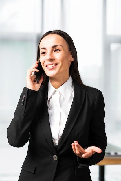 Uśmiechnięty młody bizneswoman bierze na telefon komórkowy wzrusza ramionami Darmowe Zdjęcia