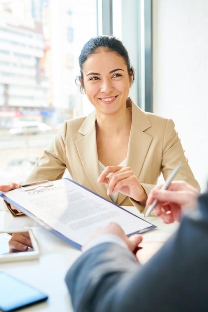 Uśmiechnięty Młody Bizneswoman Przedstawia Kontrakt Premium Zdjęcia