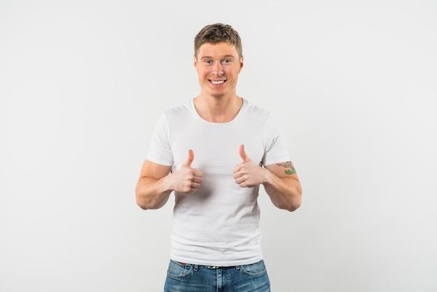 Uśmiechnięty młody człowiek pokazuje kciuk up z dwa rękami przeciw białemu tłu Darmowe Zdjęcia