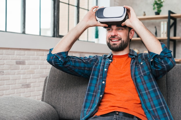 Uśmiechnięty młody człowiek siedzi na kanapie sobie aparat wirtualnej rzeczywistości Darmowe Zdjęcia