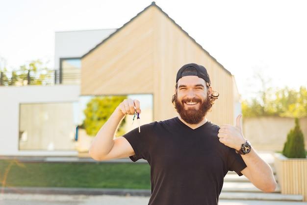 Uśmiechnięty Młody Człowiek Trzyma Klucze Do Domu I Pokazuje Kciuk Do Góry Premium Zdjęcia