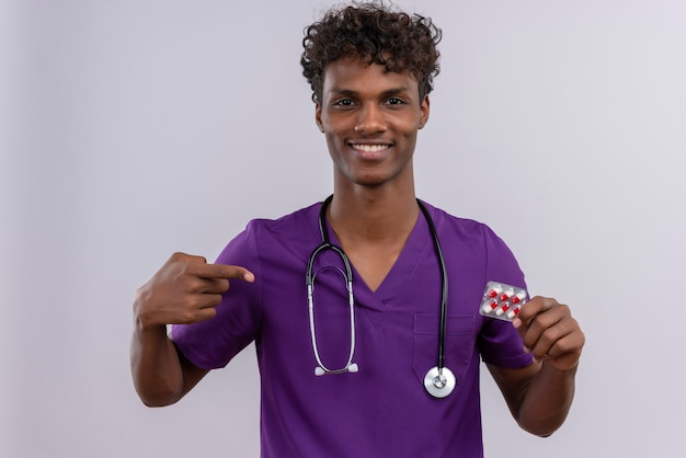 Uśmiechnięty Młody Przystojny Ciemnoskóry Lekarz Z Kręconymi Włosami W Fioletowym Mundurze Ze Stetoskopem Wskazującym Na Tabletki Palcem Wskazującym Darmowe Zdjęcia
