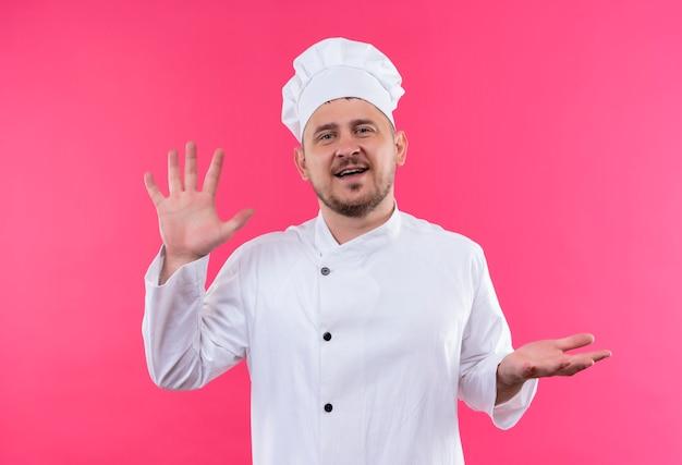 Uśmiechnięty Młody Przystojny Kucharz W Mundurze Szefa Kuchni Pokazuje Puste Ręce Na Białym Tle Na Różowej Przestrzeni Darmowe Zdjęcia