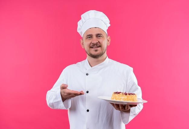 Uśmiechnięty Młody Przystojny Kucharz W Mundurze Szefa Kuchni Trzymając Talerz Ciasta, Wskazując Na To Ręką Na Białym Tle Na Różowej Przestrzeni Darmowe Zdjęcia