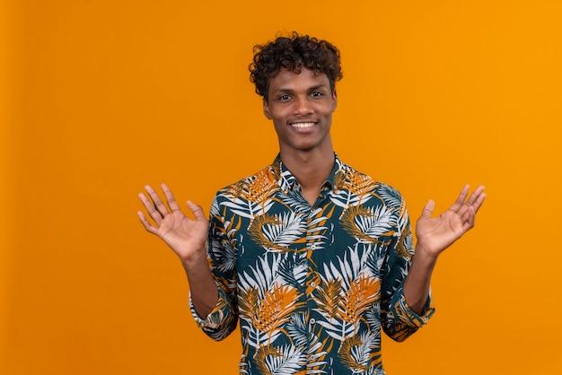 Uśmiechnięty Młody Przystojny Mężczyzna W Koszuli, Otwierając Szeroko Otwarte Ramiona Patrząc Na Pomarańczowym Tle Darmowe Zdjęcia