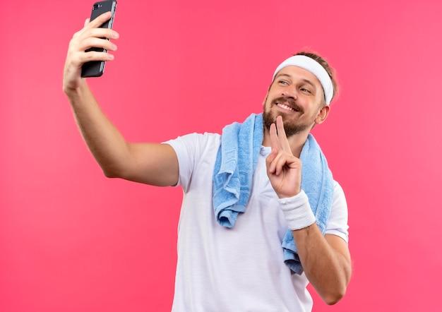 Uśmiechnięty Młody Przystojny Sportowy Mężczyzna Ubrany W Opaskę I Opaski Robi Znak Pokoju, Biorąc Selfie Z Ręcznikiem Na Szyi Na Białym Tle Na Różowej Przestrzeni Darmowe Zdjęcia