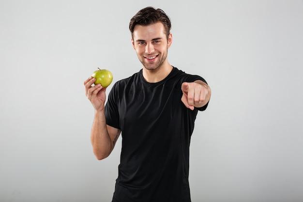 Uśmiechnięty Młody Sporta Mężczyzna Mienia Jabłko Wskazuje Przy Tobą. Darmowe Zdjęcia