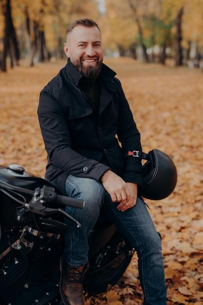 Uśmiechnięty Motocyklista Uśmiecha Się Radośnie, Trzyma Kask, Pozuje Na Motocyklu, Nosi Czarną Kurtkę I Dżinsy, Przejeżdża Przez Park Premium Zdjęcia