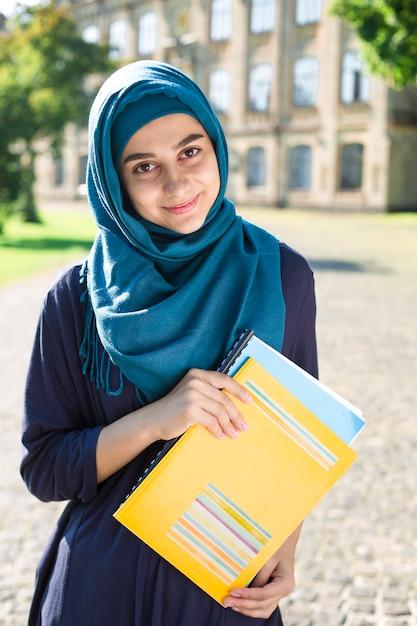 Uśmiechnięty muzułmański młody żeńskiego ucznia mienie rezerwuje stać blisko szkoły wyższa. szczęśliwa arabska dziewczyna w hidżabie. azjatycka kobieta na szkoleniu. Premium Zdjęcia