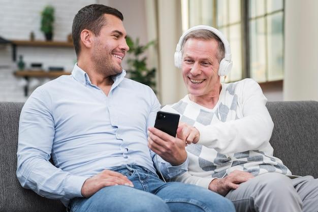 Uśmiechnięty Ojciec I Syn Siedzi Na Kanapie Darmowe Zdjęcia
