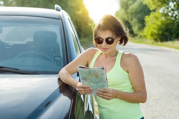 Uśmiechnięty piękny kobieta podróżnik patrzeje w turystyczną mapę Premium Zdjęcia
