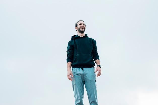 Uśmiechnięty Portret Mężczyzna Pozycja Przeciw Niebieskiemu Niebu Darmowe Zdjęcia