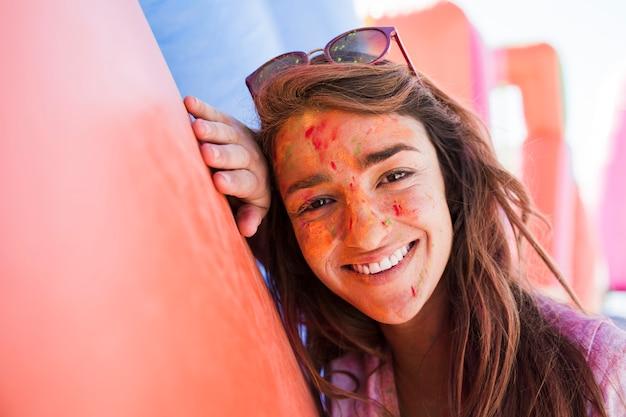 Uśmiechnięty Portret Młoda Kobieta Patrzeje Kamerę Z Holi Kolorami Na Twarz Proszku Darmowe Zdjęcia