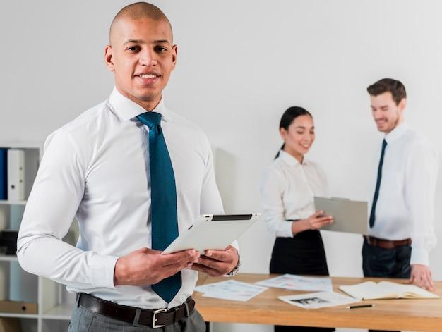 Uśmiechnięty portret młody biznesmen trzyma cyfrową pastylkę w ręce i jego kolega pracuje w tle Darmowe Zdjęcia