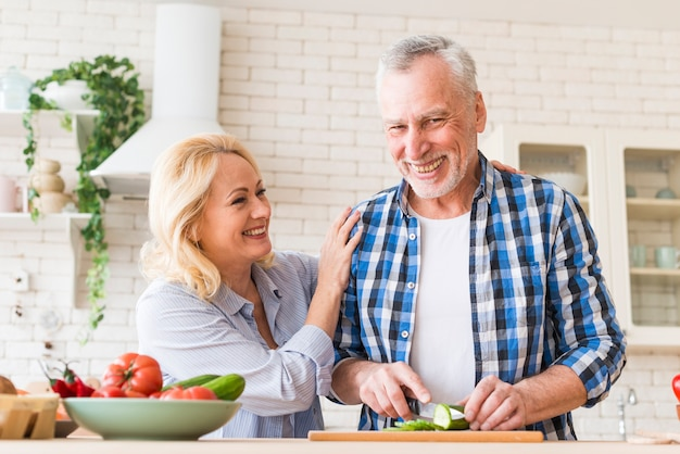 Uśmiechnięty portret starszej pary przygotowywać jedzenie w kuchni Darmowe Zdjęcia
