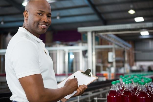 Uśmiechnięty Pracownik Płci Męskiej Odnotowujący Produkty W Fabryce Soków Darmowe Zdjęcia