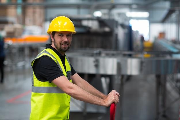 Uśmiechnięty Pracownika Fabrycznego Ciągnięcia Tramwaj W Fabryce Premium Zdjęcia