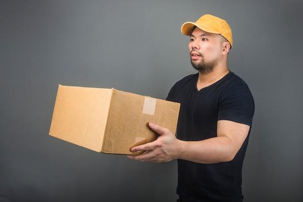 Uśmiechnięty przystojny azjatykci doręczeniowy mężczyzna jest ubranym nakrętkę, daje i niesie pakuneczek, karton, poruszającego domowego dzień i ekspresowej dostawy pojęcie Premium Zdjęcia