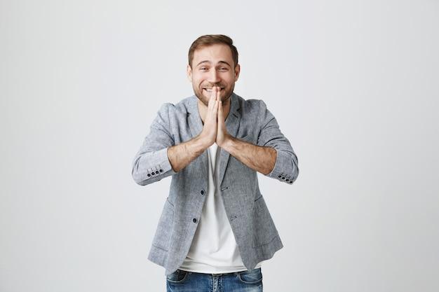 Uśmiechnięty Przystojny Mężczyzna Trzyma Się Za Ręce W Modlitwie, Prosząc O Pomoc Lub Dziękując Darmowe Zdjęcia