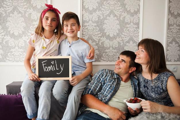 Uśmiechnięty Rodzic Patrzeje Ich Dzieci Trzyma łupek Z Rodzinnym Tekstem Darmowe Zdjęcia