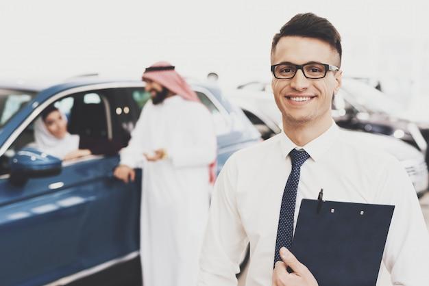 Uśmiechnięty sprzedawca samochodów w auto salon vip arab clients. Premium Zdjęcia