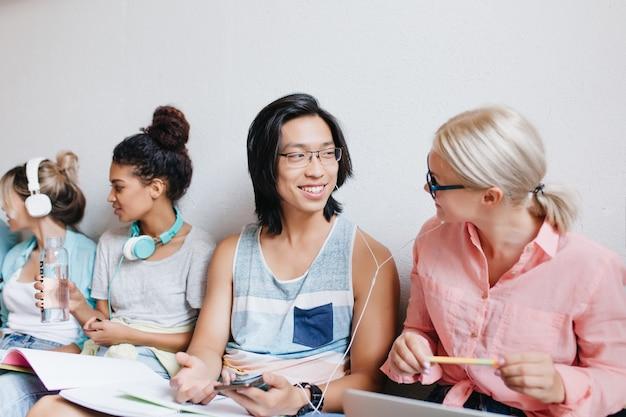 Uśmiechnięty Student Azjatycki Omawiający Ulubioną Piosenkę Z Blondynką Podczas Przygotowywania Lekcji. Wewnątrz Portret Zadowolonych Przyjaciół Ze Studiów Rozmawiających O Egzaminach I Słuchanie Muzyki W Białych Słuchawkach. Darmowe Zdjęcia