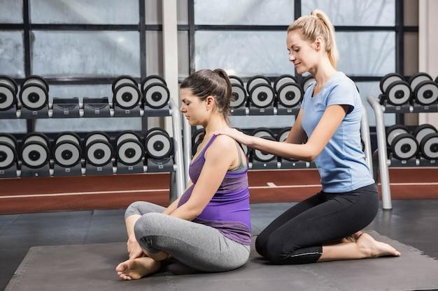 Uśmiechnięty Trener Masuje Kobieta W Ciąży Przy Gym Premium Zdjęcia