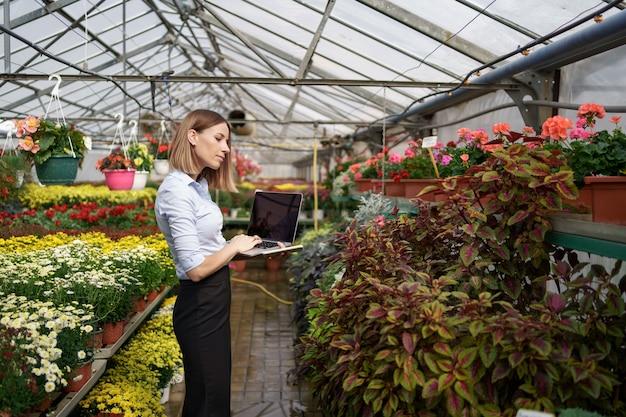 Uśmiechnięty Właściciel Szklarni Pozuje Z Laptopem W Dłoniach Rozmawia Przez Telefon Mając Wiele Kwiatów I Szklany Dach. Darmowe Zdjęcia