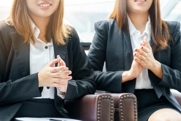 Uśmiechu Bizneswoman Klascze Ręki Podczas Gdy Siedzący Pojęcie. Premium Zdjęcia