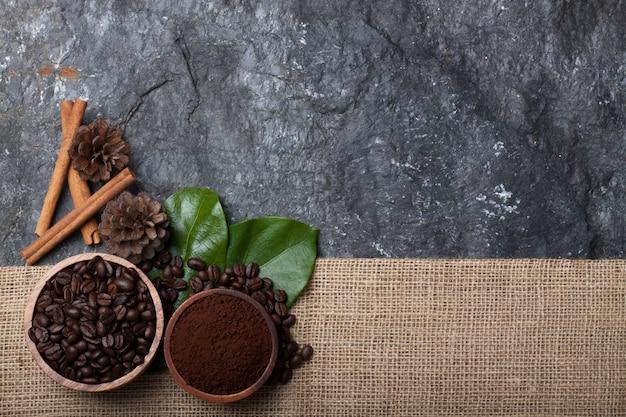 Ustaw Płaskie Ziarna Kawy W Filiżance Z Drewna Na Zielonym Liściu, Sosna Na Płótnie Na Czarnym Kamieniu Premium Zdjęcia