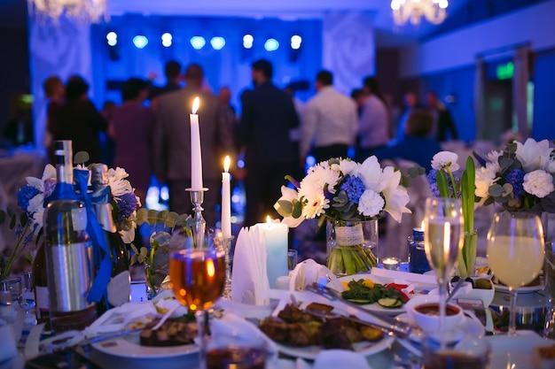 Ustawienia Stołu Weselnego W Restauracji. Ludzie Tańczący W Tle Stołu Dla Nowożeńców. Premium Zdjęcia