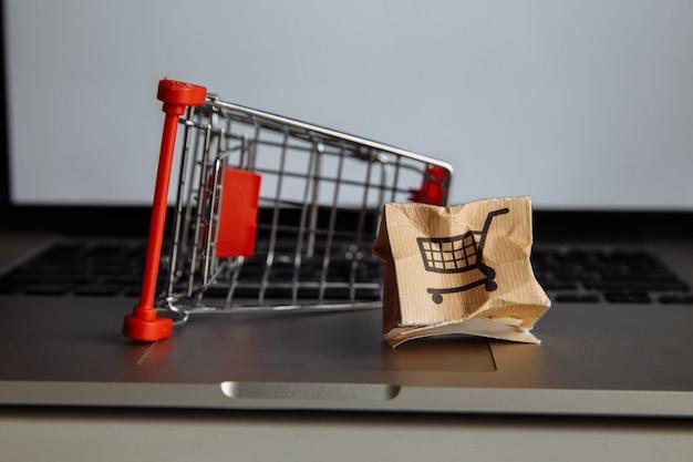Uszkodzone Pudełko Papierowe I Koszyk Na Klawiaturze Laptopa. Koncepcja Zakupów I Dostawy Online. Premium Zdjęcia