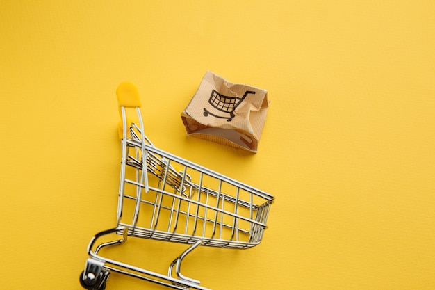 Uszkodzone Pudełko Papierowe I Koszyk Na żółtym Tle. Koncepcja Dostawy. Wypadek Podczas Transportu. Premium Zdjęcia