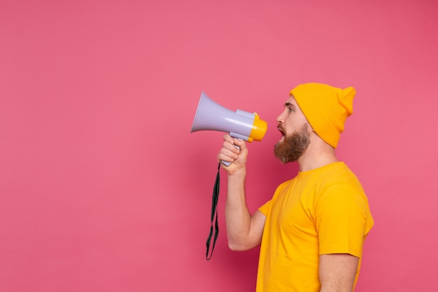 Uwaga! Europejski Mężczyzna Krzyczy W Megafon Na Różowym Tle Darmowe Zdjęcia
