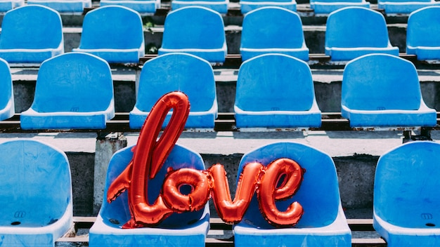 Uwielbiam Czerwony Balon Foliowy Na Niebieskich Siedzeniach Stadionu Premium Zdjęcia
