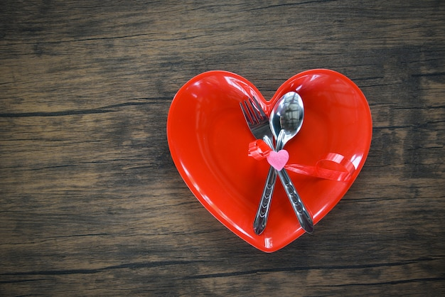 Valentines dinner romantic love concept romantyczny stół ustawienie ozdobione łyżką widelca w czerwone serce płytki na drewnianych Premium Zdjęcia