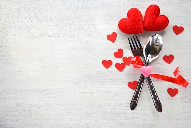 Valentines dinner romantyczna koncepcja miłość romantyczny stół ustawienie ozdobione łyżką widelca i czerwone serce na białym drewnianym Premium Zdjęcia