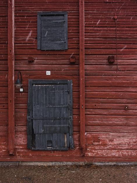 Vertical Strzał Czerwona Drewniana ściana Z Szarymi Drewnianymi Drzwiami W Zimie Darmowe Zdjęcia
