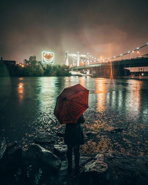 Vertical Strzał Kobieta Trzyma Czerwoną Parasolową Pozycję Blisko Jeziora W Mieście Podczas Nocy Darmowe Zdjęcia