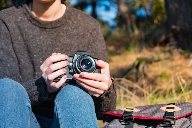 Vintage Kamera Filmowa W Rękach Kobiet. Bliska Strzał Kobiety Trzymającej Kamerę Na Zewnątrz Premium Zdjęcia