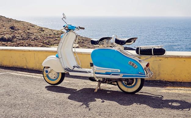 Vintage niebiesko-biały dwumiejscowy skuter zaparkowany na ulicy Premium Zdjęcia