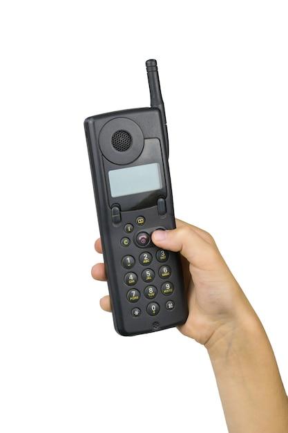 Vintage Telefon Komórkowy W Prawej Dłoni Dziecka Na Białym Tle Na Białej Powierzchni. Retro środki Komunikacji. Technologia Z Przeszłości. Premium Zdjęcia
