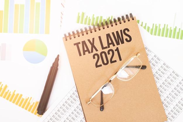 W Notesie Rzemieślniczym Znajduje Się Napis Tax Laws 2021, Obok Ołówków, Okularów, Wykresów I Diagramów. Premium Zdjęcia
