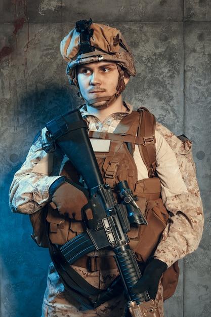 W pełni wyposażony żołnierz armii w kamuflażu i hełmie, uzbrojony w pistolet i karabin szturmowy Premium Zdjęcia
